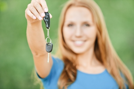 stretched out: portrait cute young woman stretched out hand car keys background nature