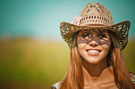 sprightly: portrait attractive young woman hat smiling background sun field Stock Photo