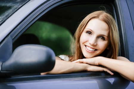 young beautiful young woman sitting car looking out open window smiling Stock Photo - 11032879