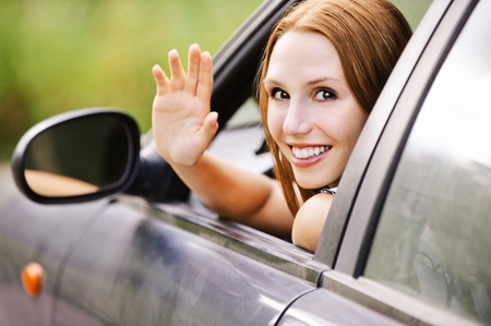 pretty young woman sitting car looking out window waving smiling photo