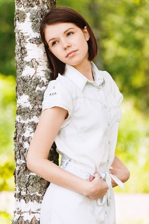 portrait beautiful sad woman leaning wood background summer green park photo