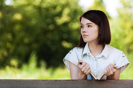portrait beautiful woman short hair book looks toward background summer green park photo