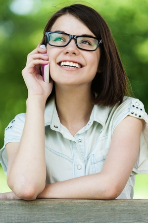 pretty young woman talking phone short hair wearing glasses background summer green park photo