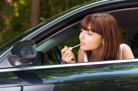 youthful: Portrait beautiful young woman sitting car peeps head out window looking mirror paints lips