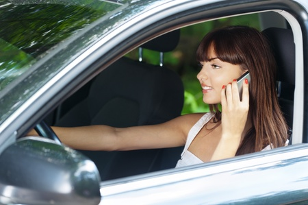 pretty young long-haired woman sitting car steering wheel talking phone smiling photo