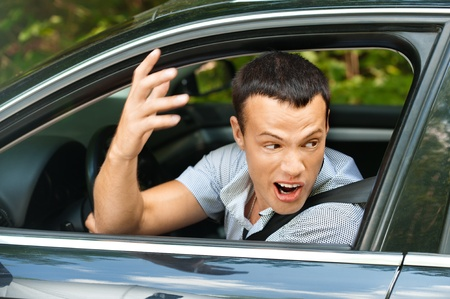 swearing: Portrait young man sitting car looking out window looks back indignantly background summer green park Stock Photo