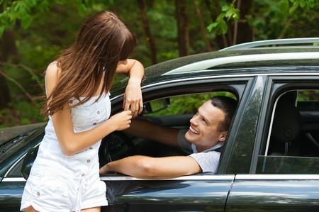 sig: coche joven apuesto hombre sentado mirando por la ventana hablando hermoso joven mujer fondo verde de verano parque Foto de archivo