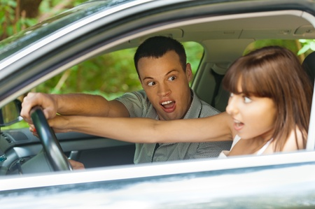 suddenness: pretty young couple man woman sitting car surprised hold hands steering wheel background summer green park