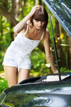 beautiful young slender woman stands next car hood open background summer green park photo