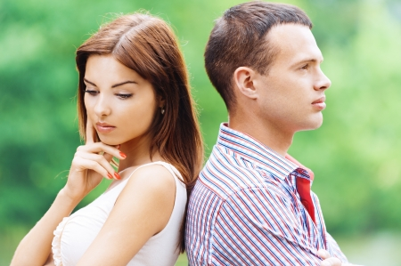 dreary: portrait beautiful young man woman couple standing back each other sad background summer green park Stock Photo