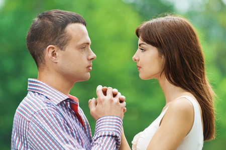 portrait young couple loving facing each other hold hands background summer green park Stock Photo