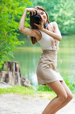 portrait young charming slender woman camera background lake summer green park photo