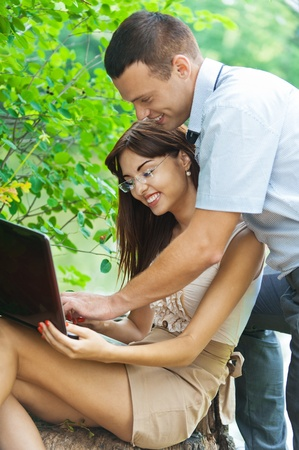 portrait young couple man woman student laptop background summer green park photo