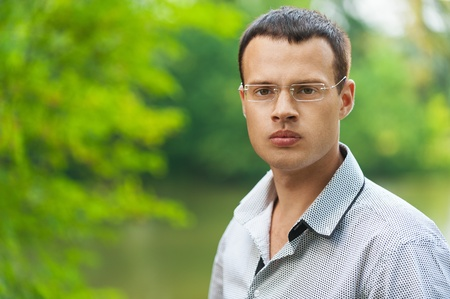 undergrad: Portrait young dark-haired man glasses serious background summer green park Stock Photo