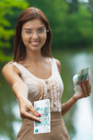portrait beautiful young woman glasses reach out money smile background lake summer green park photo