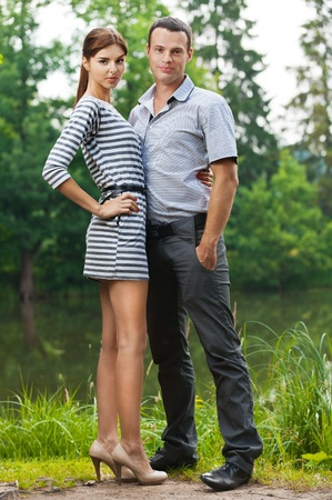 portrait young couple love woman man full-length background pond summer green park photo