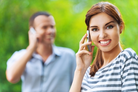 portrait young beautiful happy couple man woman talking phone background summer green park photo