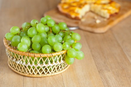 mouthwatering: wicker basket bunch green grapes cutting wooden board cake background wooden table Stock Photo