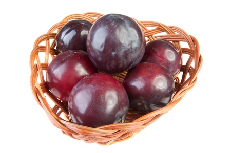 six plums wicker basket background isolated photo