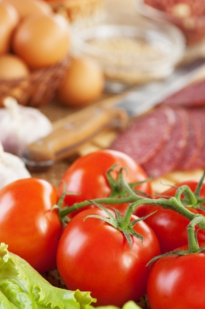 appetizing foods ( twig red tomatoes,lettuce, garlic, sausage, eggs and seasonings) background table photo