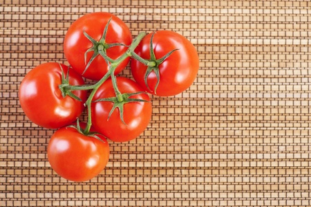 closeup twig five red tomatoes background wooden table photo