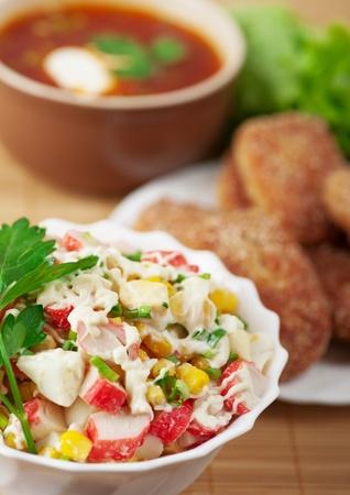 delicious dinner closeup bowl(crab salad,burgers,borscht) background wooden table Stock Photo - 11254740