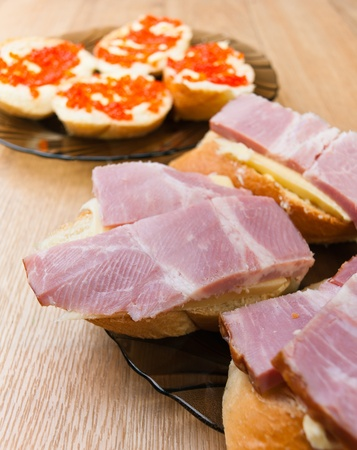 closeup sandwiches red caviar , cheese, ham background wooden table Stock Photo - 11254373