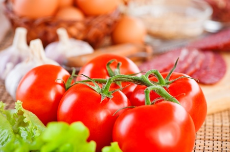 knife tomato: foods (tomatoes, lettuce, garlic, spices,sausage, eggs)