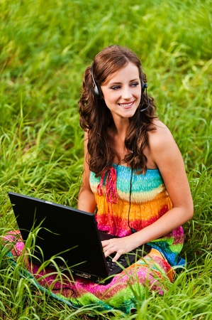 woman young beautiful sitting grass laptop headphones background lawn green grass photo