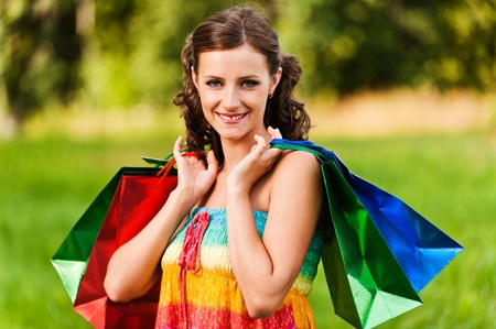 Portrait pretty young woman standing keeps shoulders shopping bags background summer green park Stock Photo - 11254858