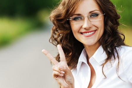 victory: portrait charming young gay woman glasses shows sign victory background road park