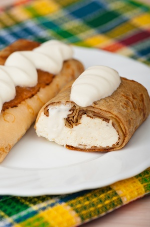 delicious pancakes with cottage cheese, raisin decorated sour cream in white plate background tablecloth checkered photo