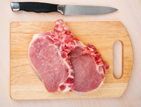 two pieces of fresh meat (pork) on cutting board, knife background wooden table photo
