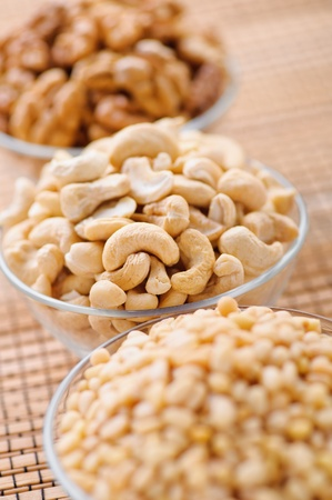 three bowls of peeled nuts (walnut, cashew, pine) on background wooden table photo