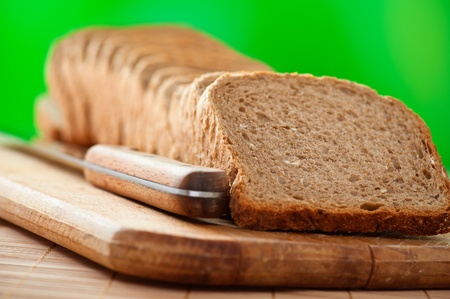 outdoors cutting board cut rye bread, knife on background wooden table Stock Photo - 11256614