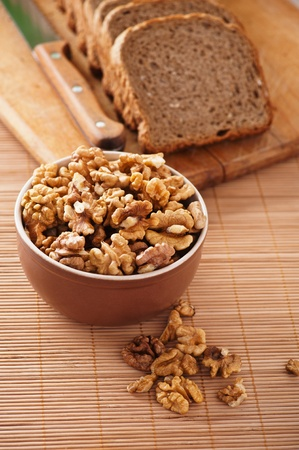 purified kernels walnuts in bowl,cutting board cut rye bread, knife background wooden table photo