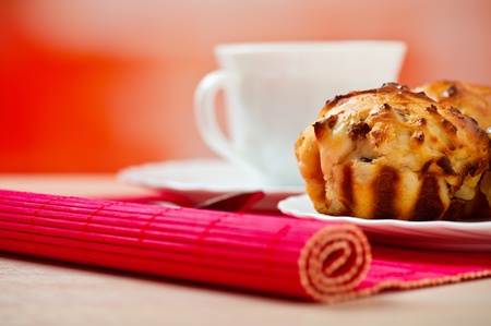 closeup cupcake, white cup (tea, coffee) on background wooden table with pink napkin photo