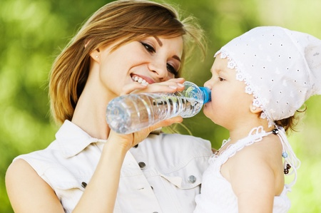 young charming caring mother gives daughter drink water bottles background summer green park photo