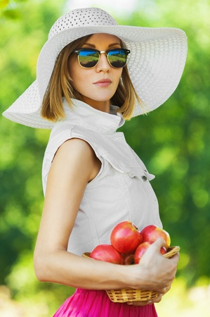 portrait beautiful young woman serious hat holds basket apples background summer green park photo