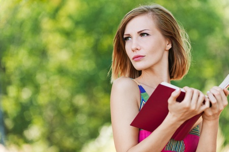 serious young beautiful short-haired woman holding red book looking sideways background summer green park photo