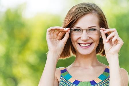 shorthaired: bello retrato de mujer divertida vasos peque�os de pelo corto de fondo verde de verano del parque Foto de archivo