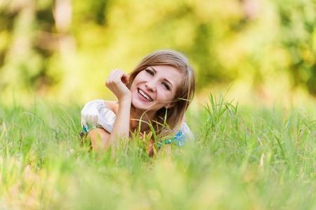 lying in grass: retrato de mujer bonita joven acostado pasto de verano descansando selva de fondo verde prado de hierba