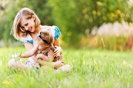 어머니의: 아름다운 젊은 어머니가 딸 편안한 좌석 잔디 배경 여름 초원 녹색 잔디 나무