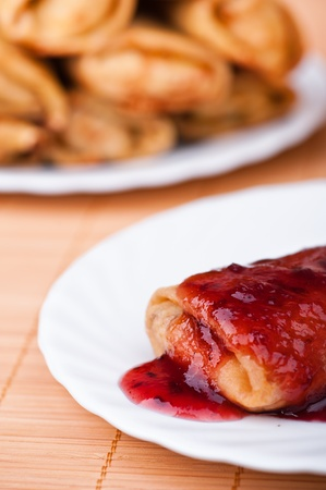 Close-up pancake with jam on saucer next to full meal of pancakes rolled up on bamboo table cloth rolls photo