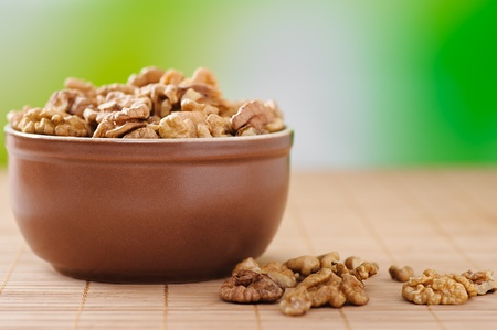 peeled walnuts in bowl of deep brown with green background, plus few scattered on bamboo table cloth Stock Photo - 11480477