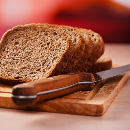 close-cut slices of rye bread on wooden cutting board, sharp knife next, all on kitchen table Stock Photo - 11480614