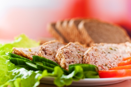 meatloaf with vegetables of cucumber and tomato salad dressed in background sliced rye bread photo