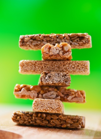 sweets piled tower (kozinaki, candied roasted nuts, peanuts and hazelnuts in icing sugar) on green background Stock Photo - 11480654