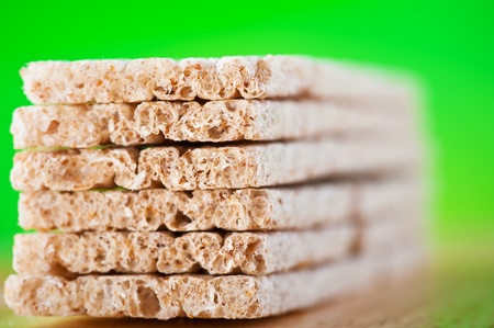 crisp loaves diet exactly stacked in piles on green background Stock Photo - 11480624