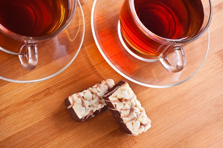 two glass transparent cups with black saucers on strong tea and chocolate cake on wooden countertop photo